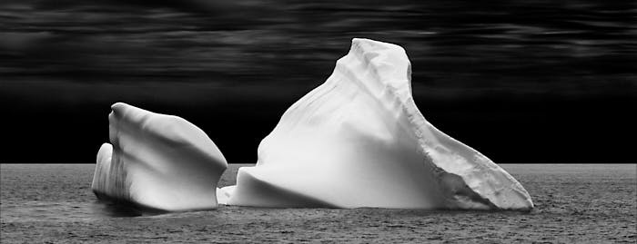 Black and white of image of curvaceous iceberg in the ocean.
